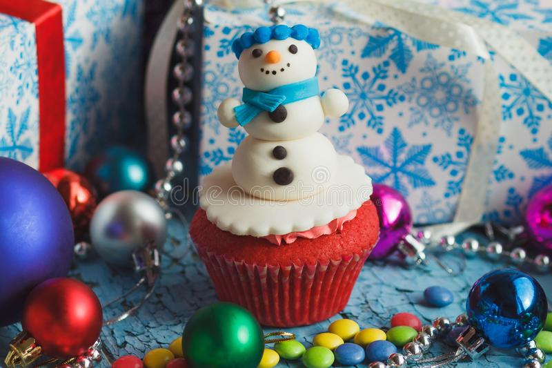 Christmas cupcake with colored decorations. Snowman made from confectionery mastic, soft focus background royalty free stock image