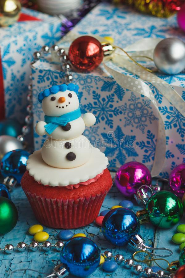 Christmas cupcake with colored decorations. Snowman made from confectionery mastic, soft focus background royalty free stock photos