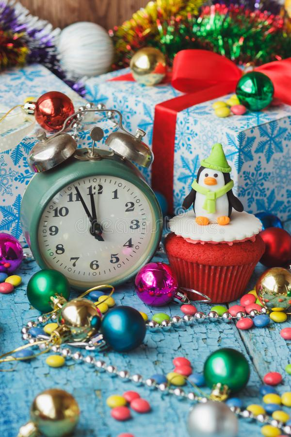Christmas cupcake with colored decorations penguin made from confectionery mastic. Soft focus background stock photo