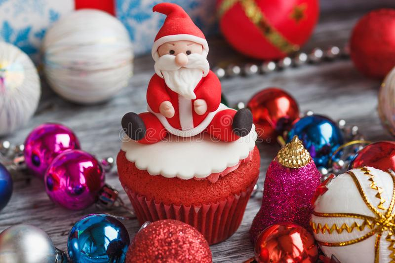 Christmas cupcake with colored decorations. Santa Claus made from confectionery mastic, soft focus background stock image