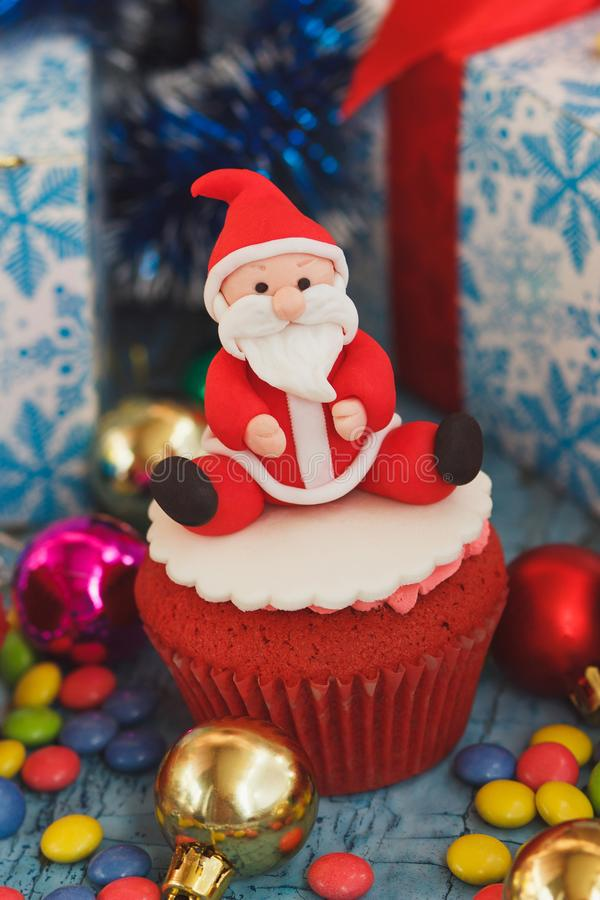 Christmas cupcake with colored decorations. Santa Claus made from confectionery mastic, soft focus background royalty free stock photos