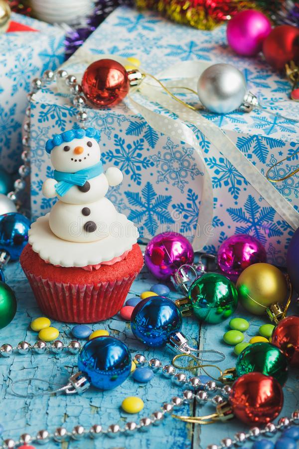 Christmas cupcake with colored decorations. Snowman made from confectionery mastic, soft focus background stock photos