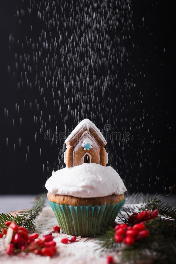 Christmas cupcake with cream and gingerbread house on black. Snow falls on the cake.  royalty free stock photo