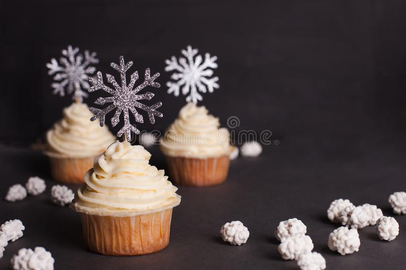 Set of winter Christmas New Year cup cakes on black background. Christmas cupcake decorated with shining snowflakes royalty free stock image