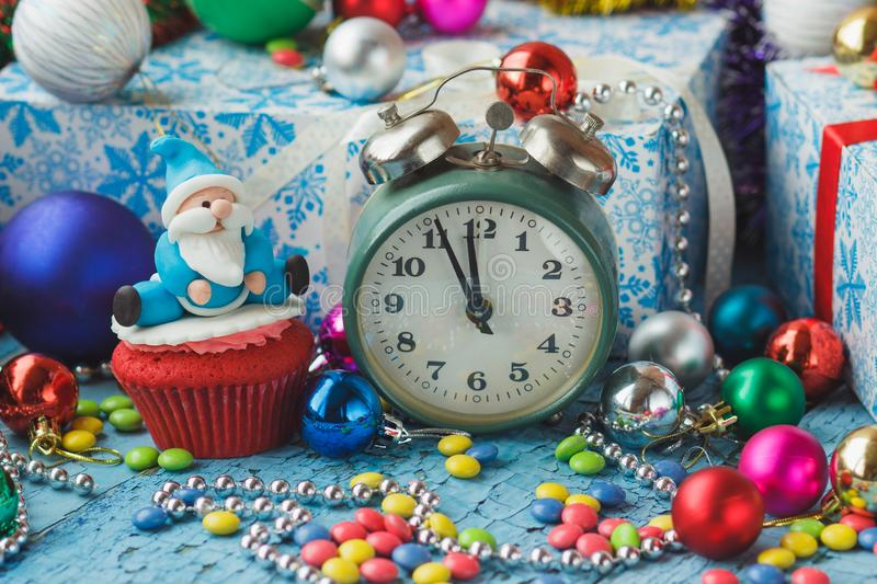 Christmas cupcake with decorative Santa made from confectionery mastic and green alarm clock. Soft focus background royalty free stock images