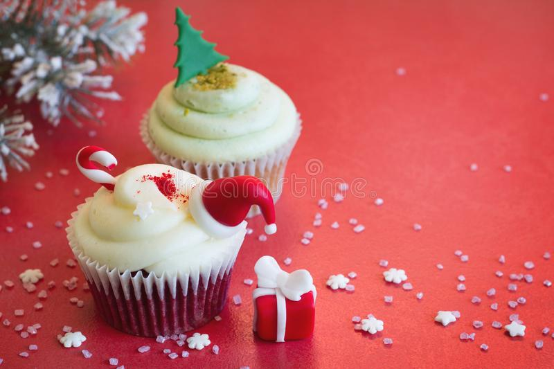 Christmas cupcake holiday ornament with fir and gift on red abstract background. Closeup stock image
