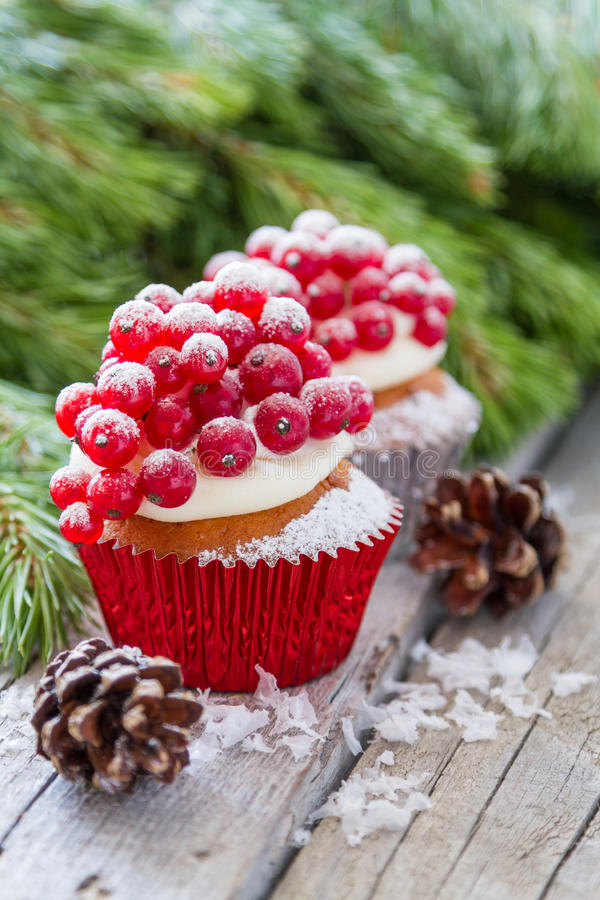 Christmas cupcake. With red berries, rustic wood background royalty free stock photos