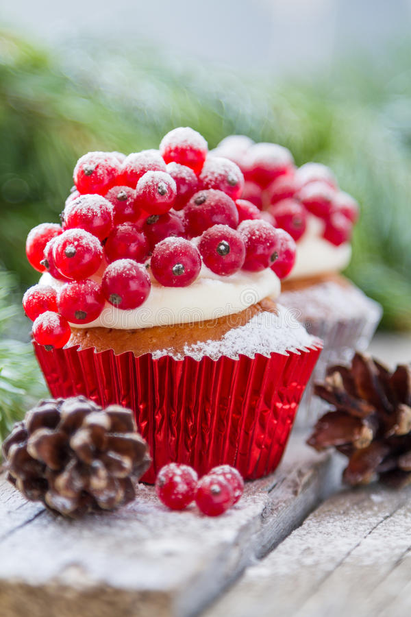 Christmas cupcake. With red berries, rustic wood background royalty free stock photography