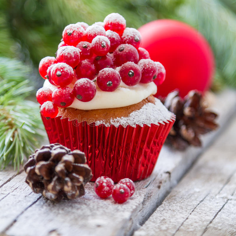Christmas cupcake. With red berries, rustic wood background stock image