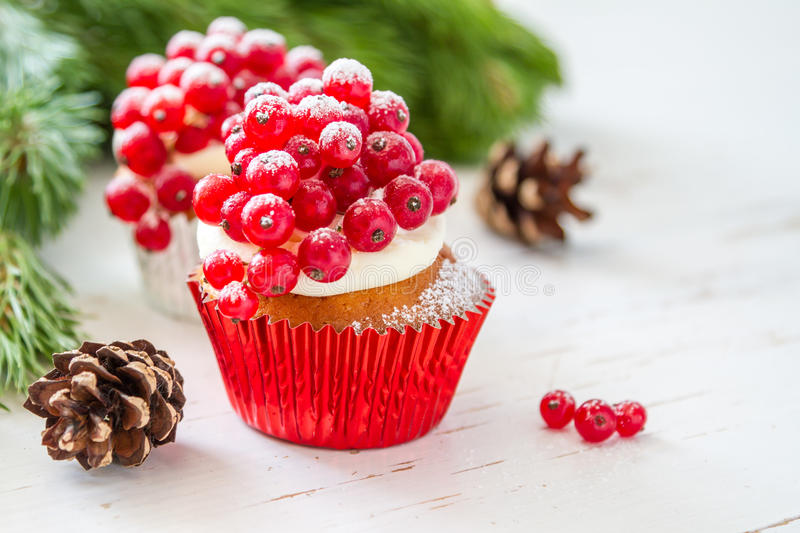 Christmas cupcake. With red berries, white wood background stock photos