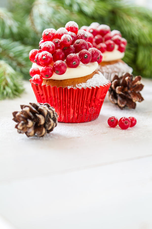 Christmas cupcake. With red berries, white wood background stock image