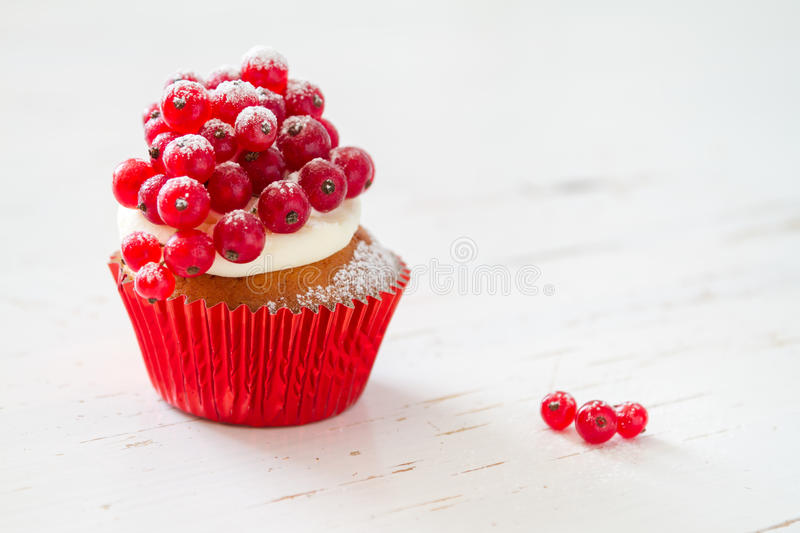 Christmas cupcake. With red berries, white wood background stock images
