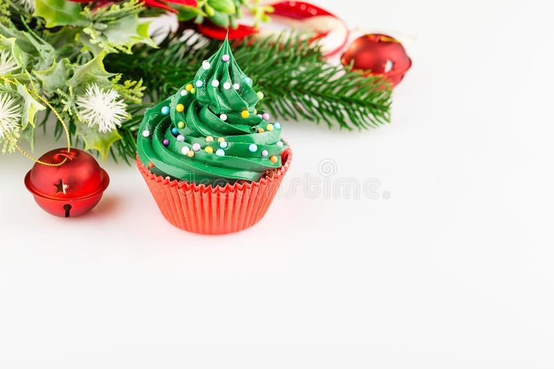 Christmas cupcake in red cup with festive decorations on white b. Christmas green cupcake with colorful sprinkles in red cup on white background with festive stock image