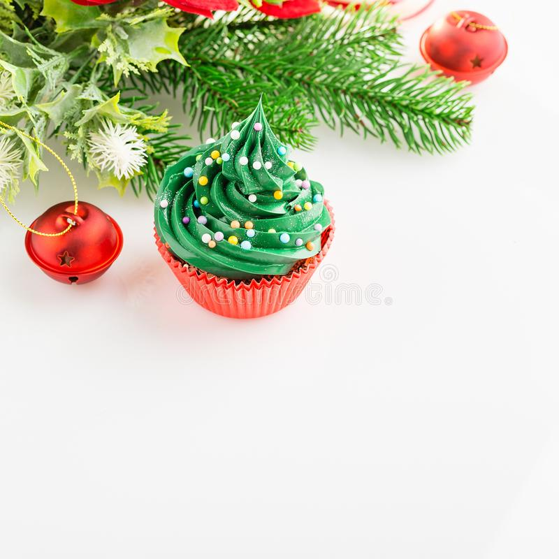 Christmas cupcake in red cup with festive decorations on white b. Christmas green cupcake with colorful sprinkles in red cup on white background with festive royalty free stock photos