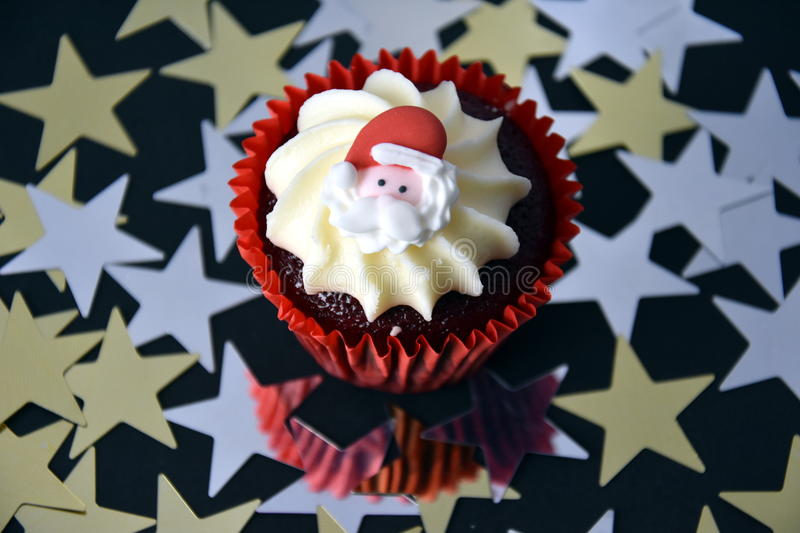 Christmas cupcake with Santa face and whipped cream topping. Xmas festive holiday food dessert. Christmas concept muffin with decoration on top and golden royalty free stock photos
