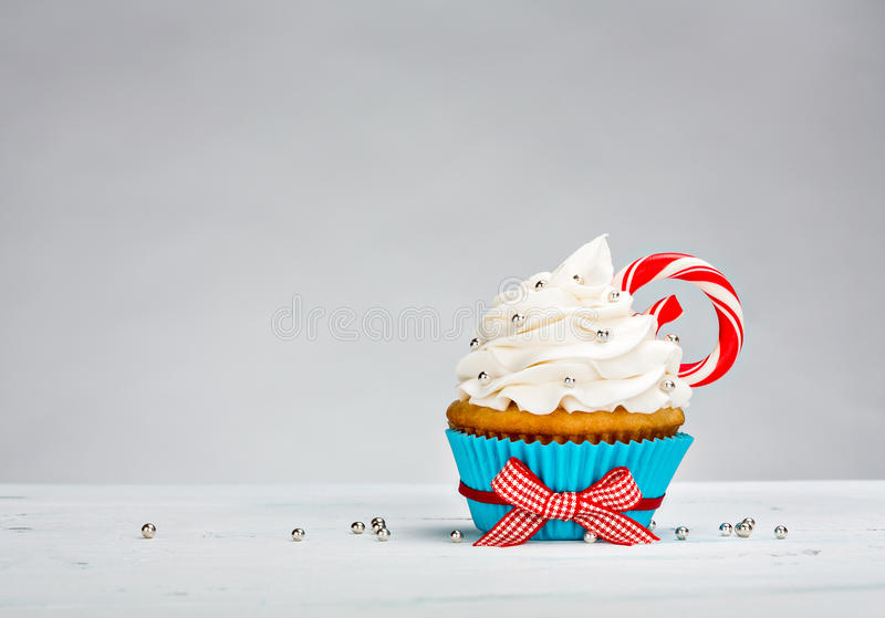 Christmas Cupcake. With vanilla buttercream icing and a Candy Cane over a white background royalty free stock photos