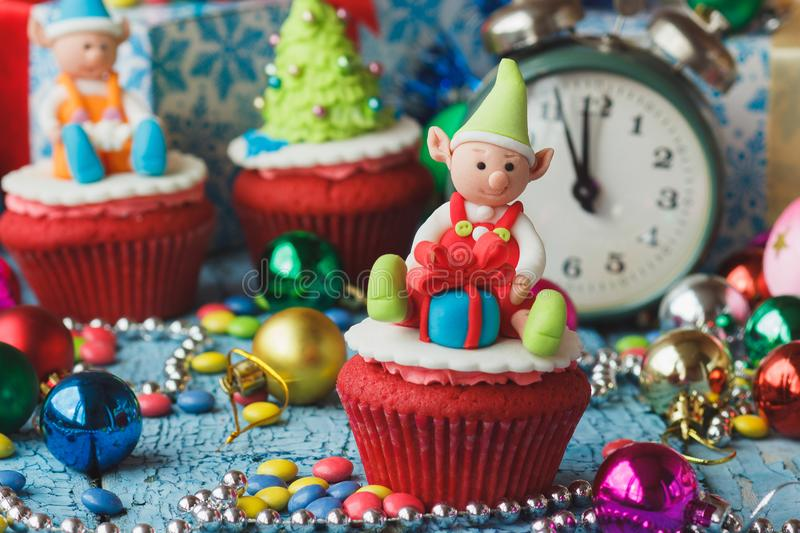 Christmas cupcakes with colored decorations. Christmas cupcake with colored decorations Elf made from confectionery mastic, soft focus background stock photo