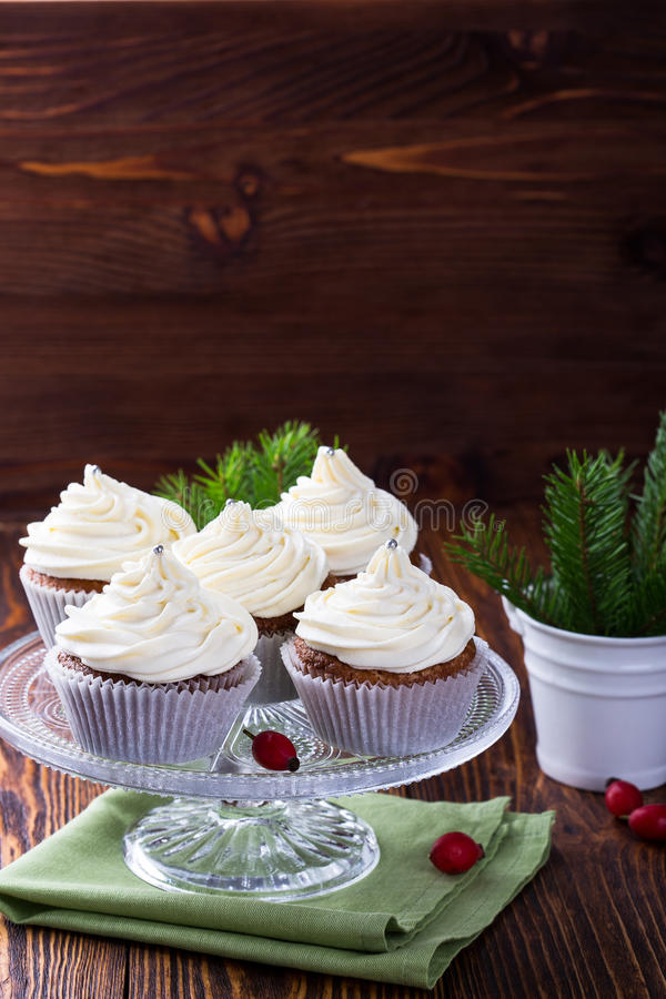 Christmas cupcakes with creamcheese frosting. Homemade christmas cupcakes with creamcheese frosting on cake stand on wooden background with spruce twigs in stock images