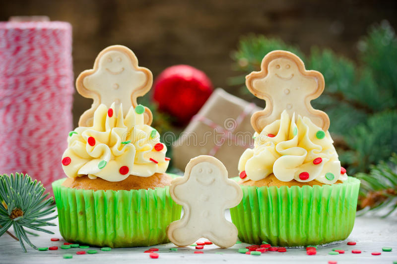 Christmas cupcakes decorated with cream, sugar confetti and gingerbread man. Cookies stock image
