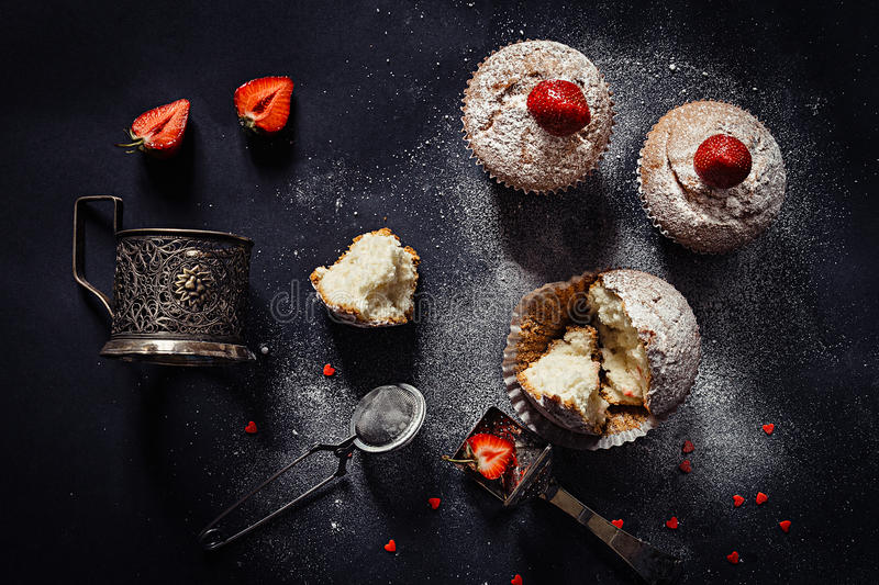 Christmas cupcakes with strawberries and powdered sugar on black background. Top view. Festive winter food backdrop stock photography