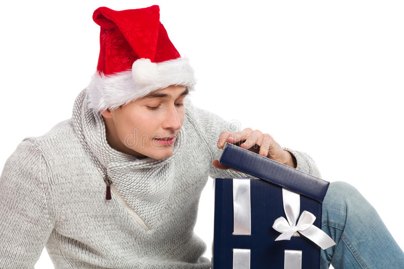 Christmas curiosity. Young man in santa's hat opening a gift. Studio portrait isolated on white stock photos