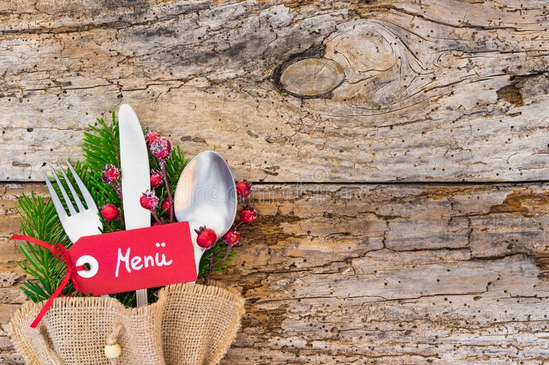 Christmas cutlery with tag and german word menue, means menu, on rustic wooden table background stock photo