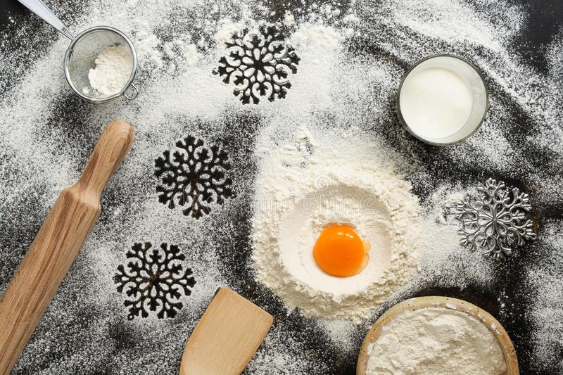Christmas dark background with baking ingredients. Flour, egg, milk, rolling pin, sieve, snowflakes, spatula. Top view, place for stock photo