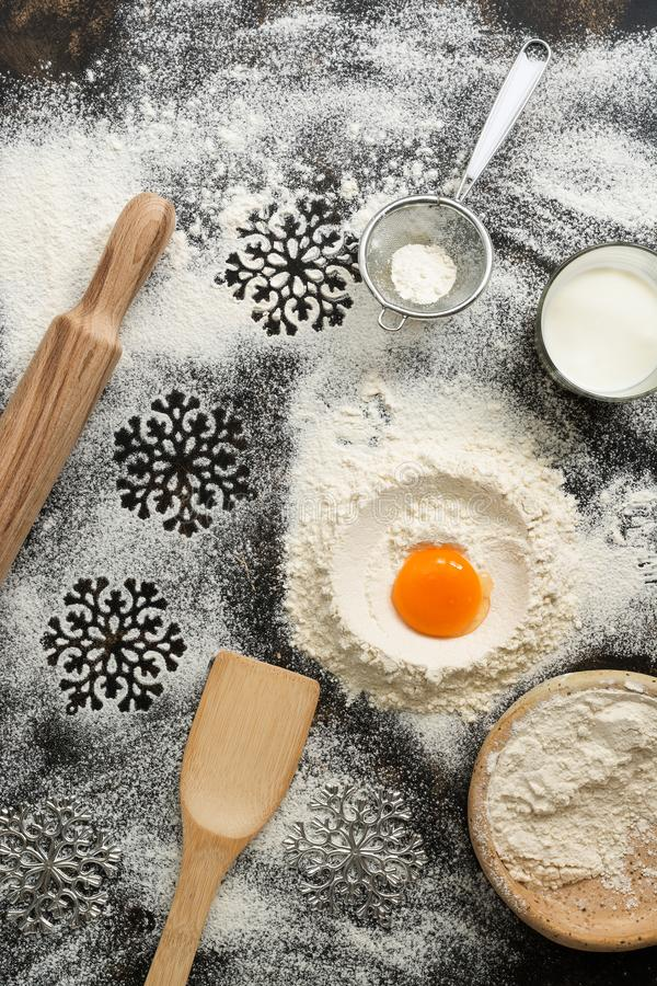 Christmas dark background with baking ingredients. Flour, egg, milk, rolling pin, sieve, snowflakes, spatula. Top view, place for royalty free stock photos