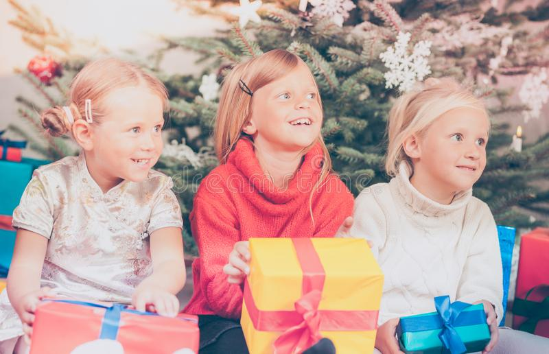 Christmas day in family, the Children unwrapping presents. Under tree royalty free stock photography