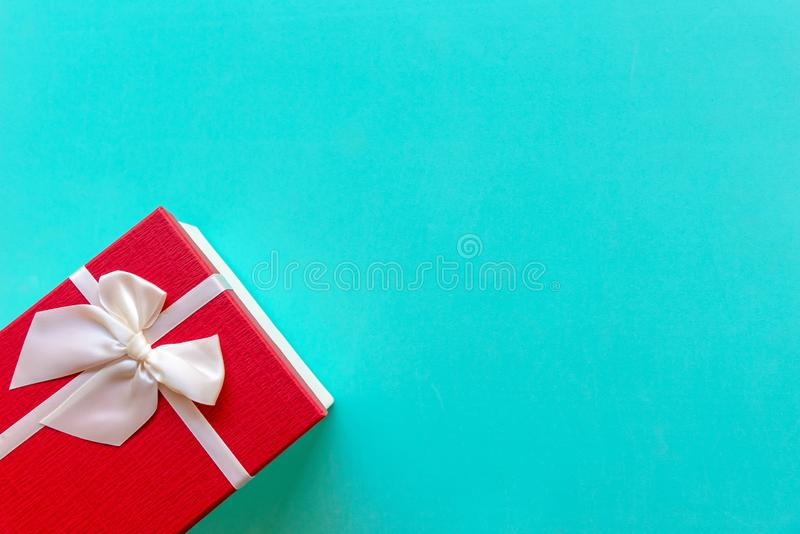 Christmas Day gift box with a red bow on blue green wall background, top view and copy space. stock images