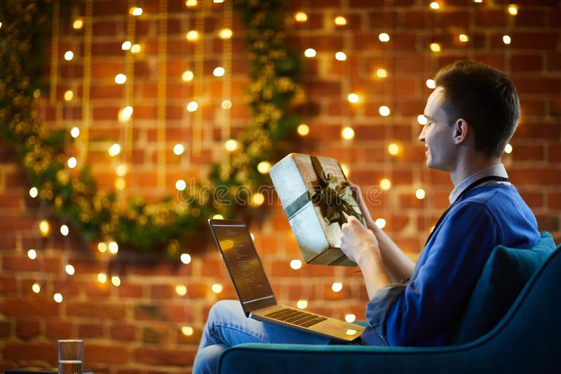 Christmas day in office. Young software engineer unpacking xmas gift in golden box while sitting in decorated office in front of laptop royalty free stock images