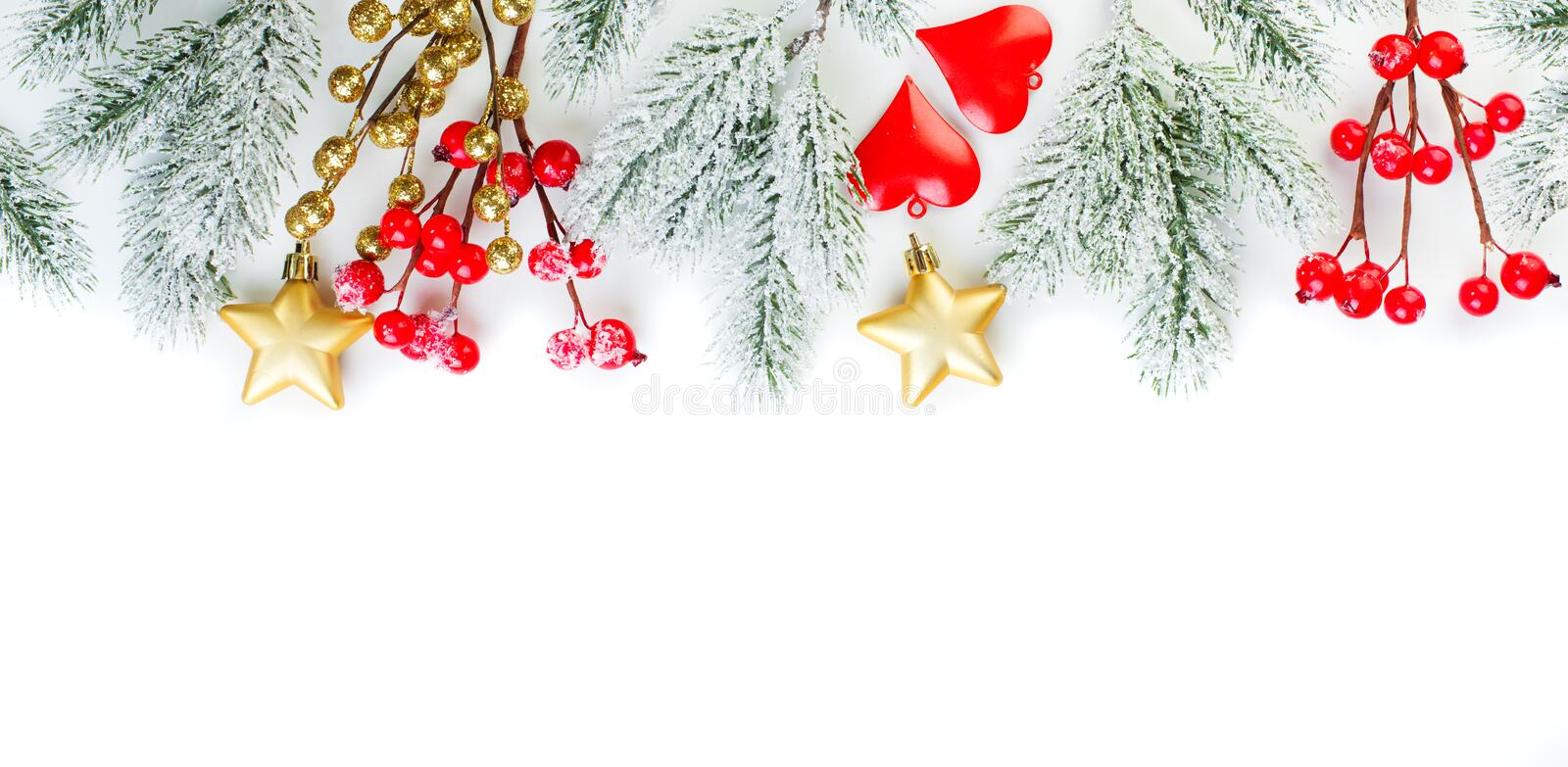Christmas decor border. Green Xmas fir branch, gold stars, red holly berries and glass baubles isolated on white background royalty free stock photos