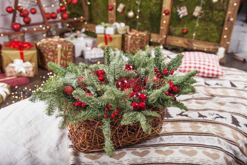 Christmas decor. Holiday basket with fir tree  branches and red balls on background og Christmas light. Winter holidays. Christmas decor. Holiday basket with fir royalty free stock photo
