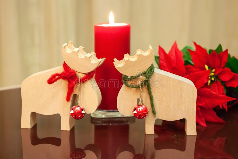 Christmas decor in modern interior. Scandinavian style, hygge. Christmas toys moose deer with red and green ropes tied around neck. And bells with lit candle royalty free stock photo
