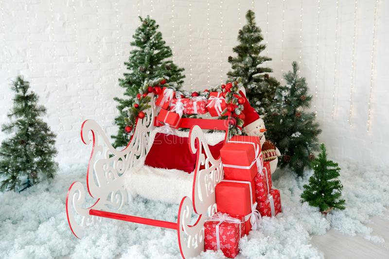 Christmas decor sleigh and red gift boxes with green christmas trees on snow, holiday decoration.  royalty free stock images