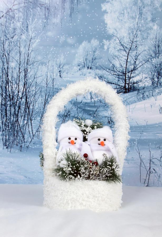Christmas decor - snowmans. In basket in winter snowy forest royalty free stock photo