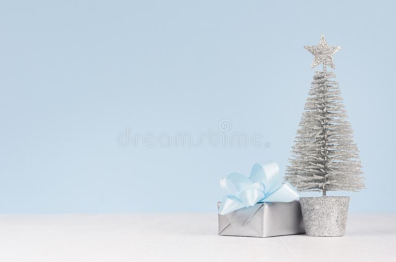 Christmas decor in soft blue color - metallic box with blue silk bow, silver tree on white wood board. Christmas decor in soft blue color - metallic box with royalty free stock image