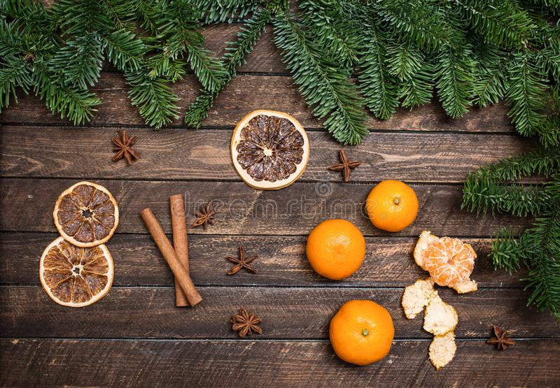 Christmas decor with tangerines, dried orange slices, anise, cinnamon sticks, branch of spruce on a wooden surface. royalty free stock image
