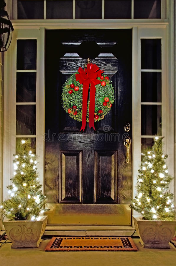 Christmas decorated front door. With small lit trees royalty free stock images