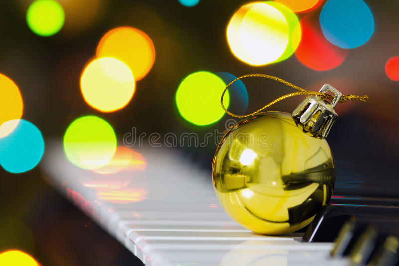 Christmas decoration. Ball on a piano against defocused lights background royalty free stock photography