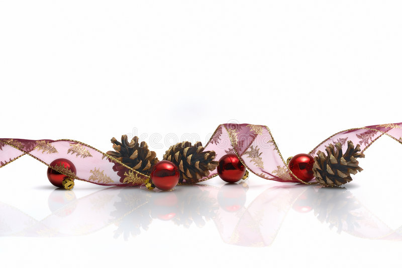 Christmas decoration. With ribbon, cones and red balls reflected on white background royalty free stock photo
