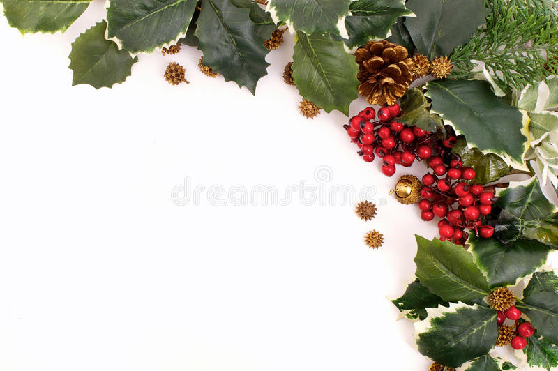 Christmas decoration arrangement with holly, berries and pine cones. Closeup christmas decoration arrangement with holly, berries and pine cones royalty free stock photos