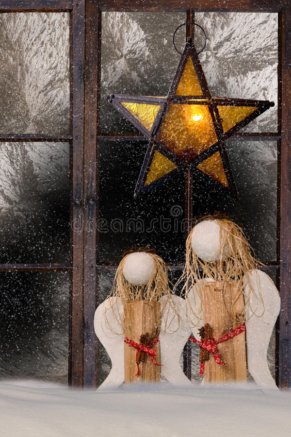 Christmas decoration, atmospheric window decoration. With shining star and two angles royalty free stock photo
