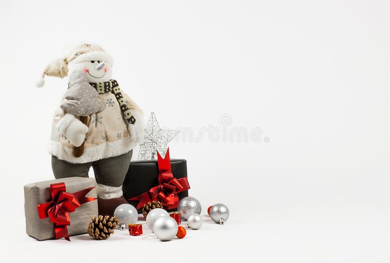 Christmas decoration background. Dressed Snowman toy pine tree in hand. xmas and christmas gifts, new year ornaments, silvery shin royalty free stock photography