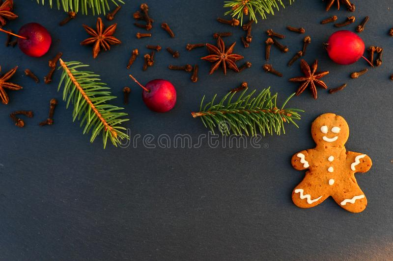 Christmas decoration background with gingerbread man cookie. Spruce branches, spices and apples on black stone board stock photography