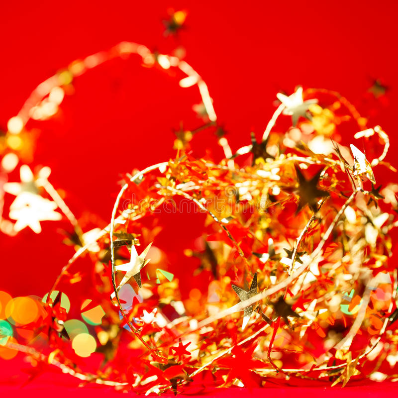 Christmas decoration background. Christmas decoration with yellow tinsel on red background royalty free stock image