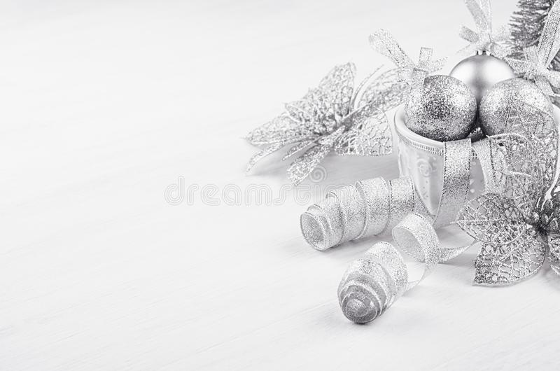 Christmas decoration - balls, curl tapes, flower of silvery glitter on white wood board. Festive home decor. stock photo