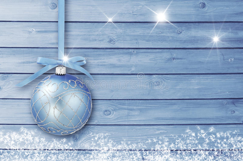 Christmas decoration on a blue wooden board with white snow, snowflakes, ice crystals. Simple Christmas, New Year card.  royalty free stock photography