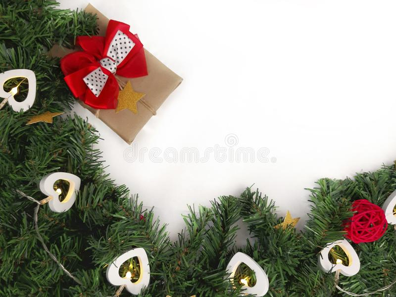 Christmas decoration border with gift, garland and fir tree on white background. Top view with copyspace royalty free stock images