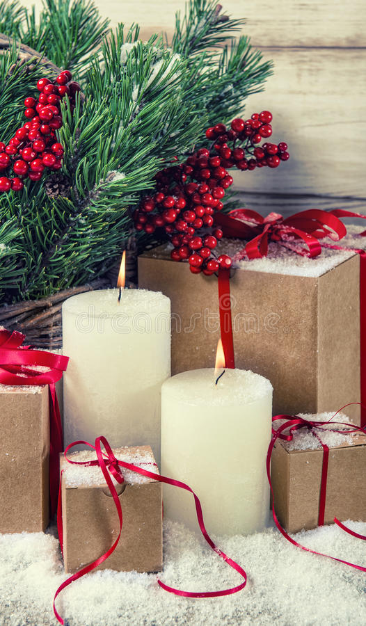 Christmas decoration with burning candles and gifts. Vintage sty stock photography